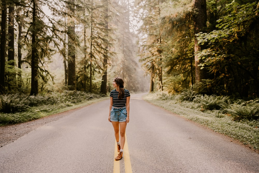 woman in black and white striped long sleeve shirt and blue denim shorts walking on gray
