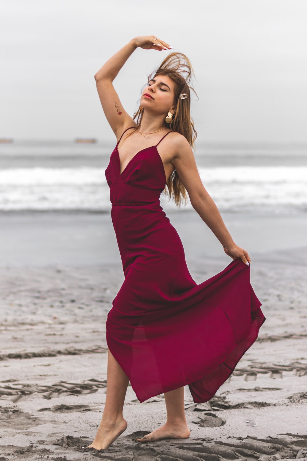 woman in red spaghetti strap dress standing on beach during daytime