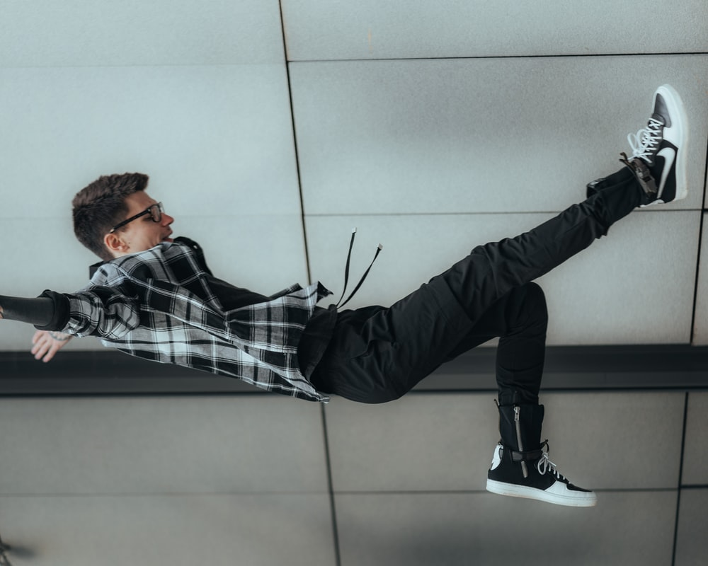 man in black and white plaid dress shirt and black pants lying on floor