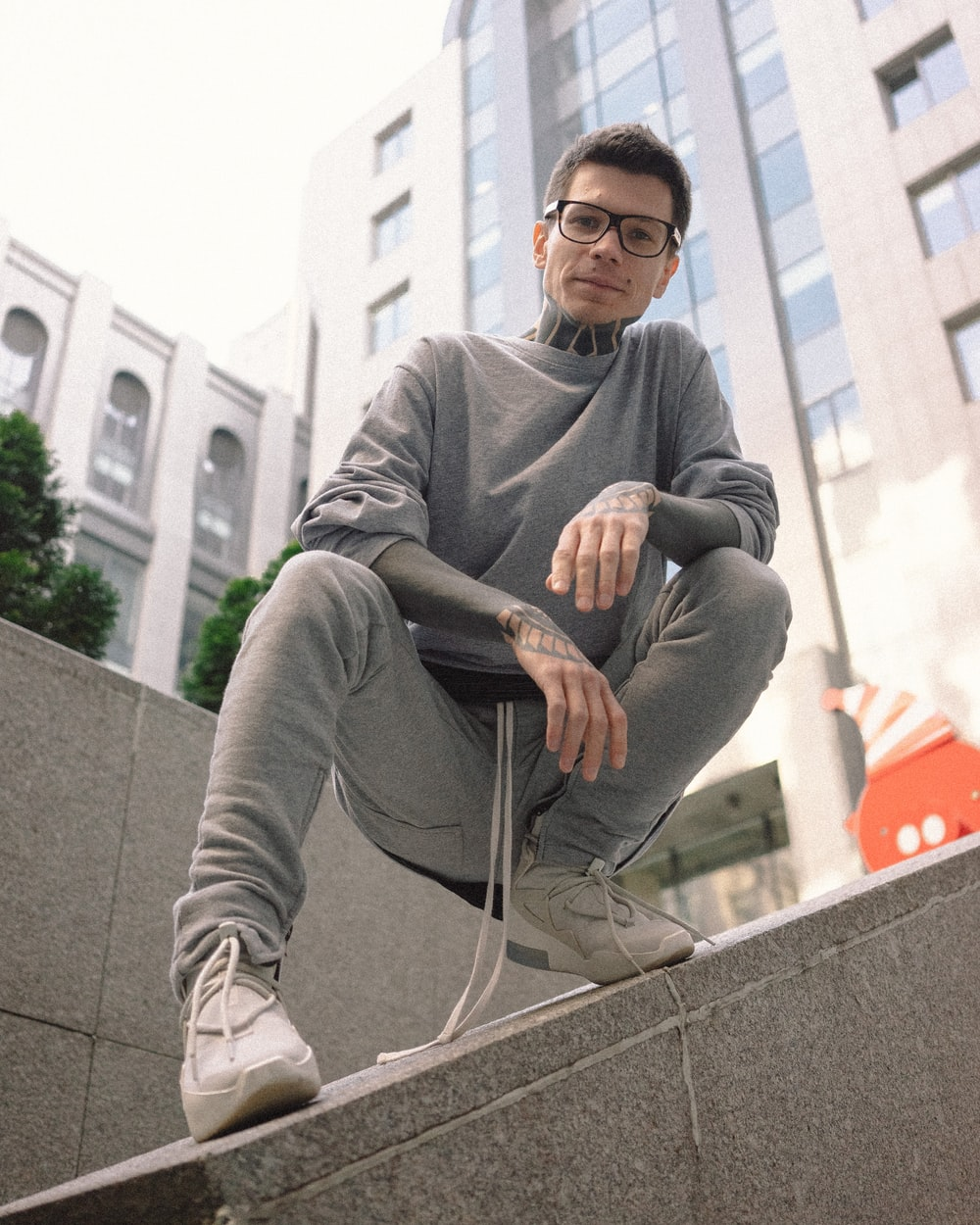 man in gray sweater sitting on gray concrete bench