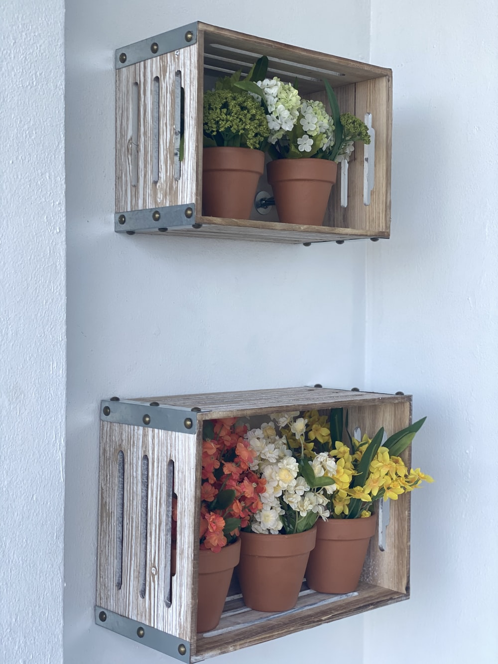yellow and orange flowers on brown wooden wall mounted rack