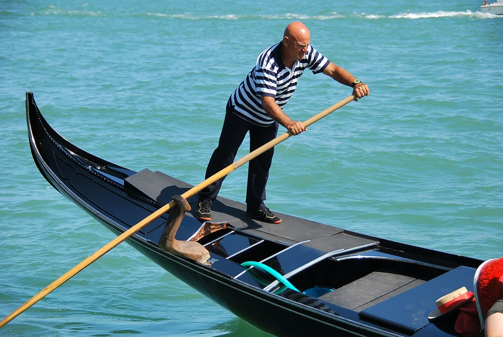 man in blue and white striped long sleeve shirt riding on black boat during daytime