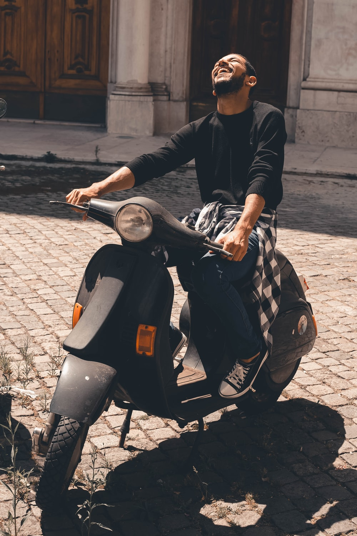 man in black leather jacket riding black motorcycle