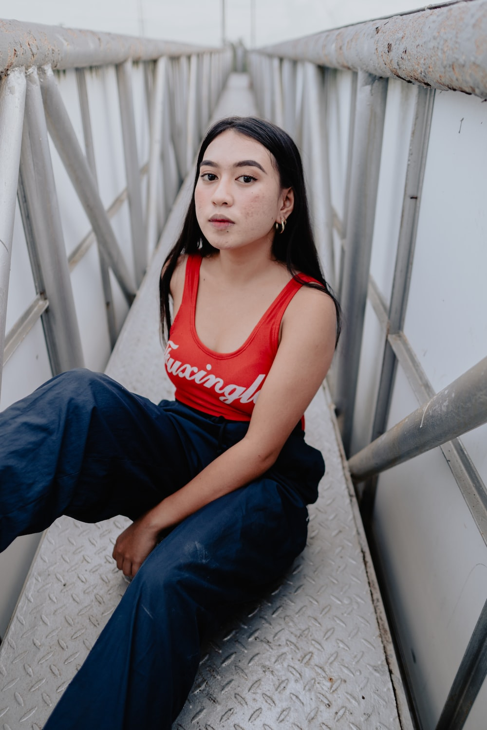 woman in red tank top and blue denim jeans sitting on white concrete wall