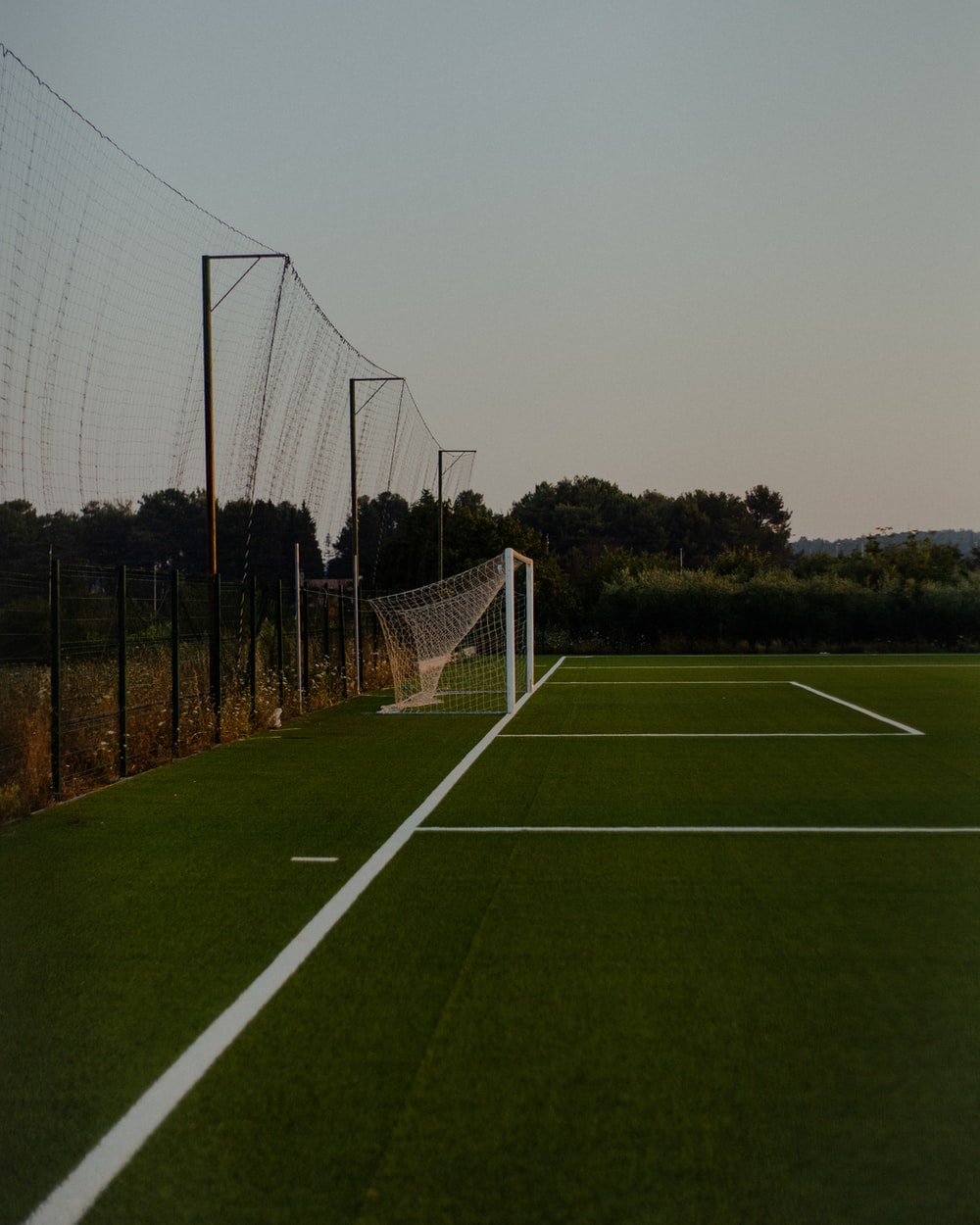 soccer goal net on green grass field during daytime