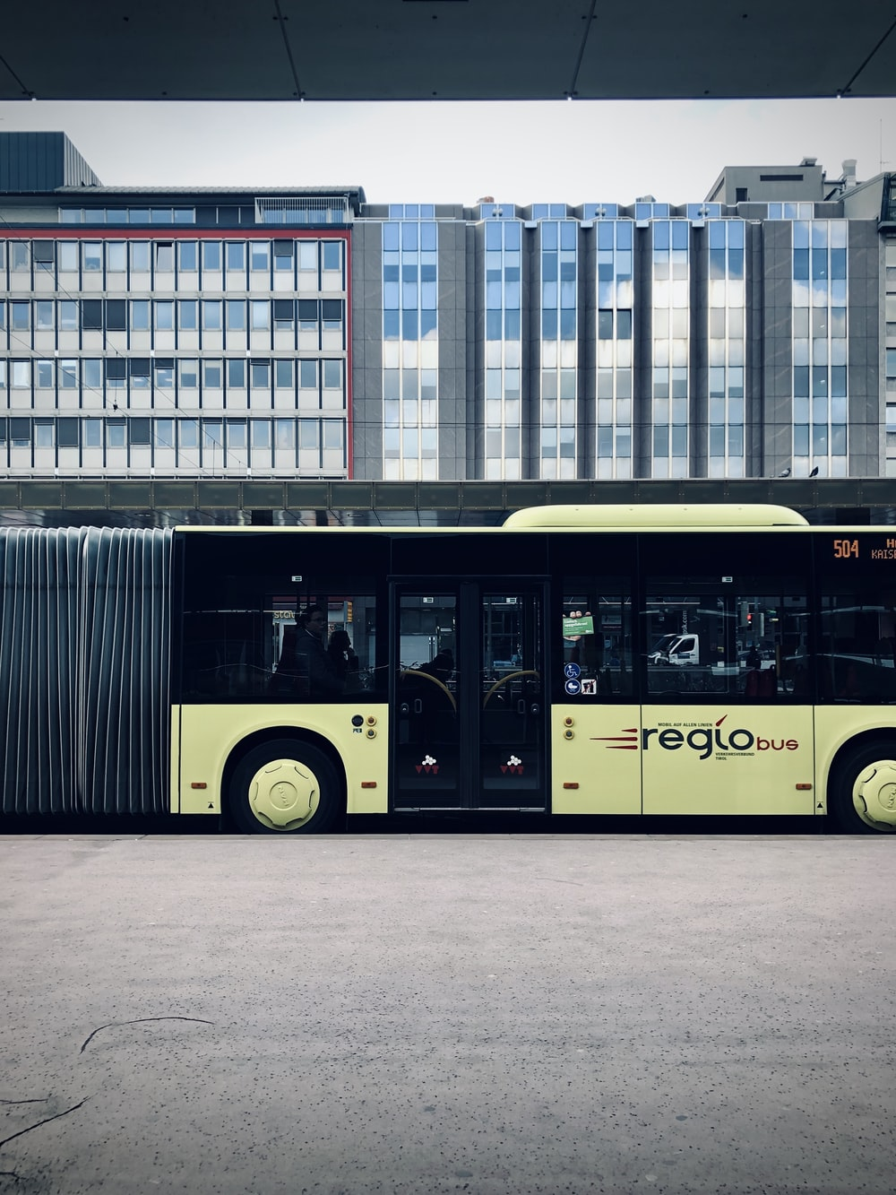 yellow bus in front of white concrete building during daytime
