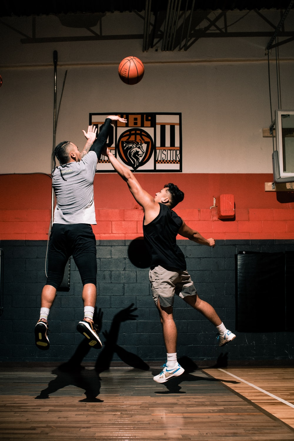 man in gray t-shirt and black pants holding basketball