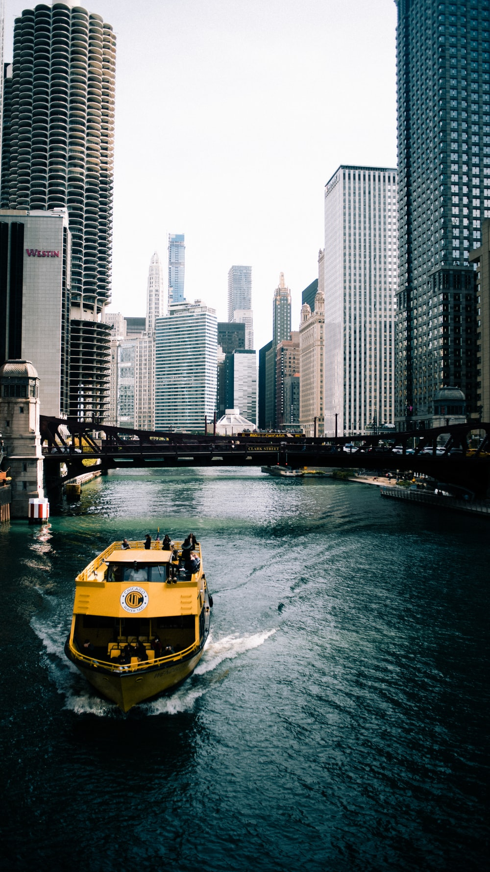 yellow and black boat on water near high rise buildings during daytime