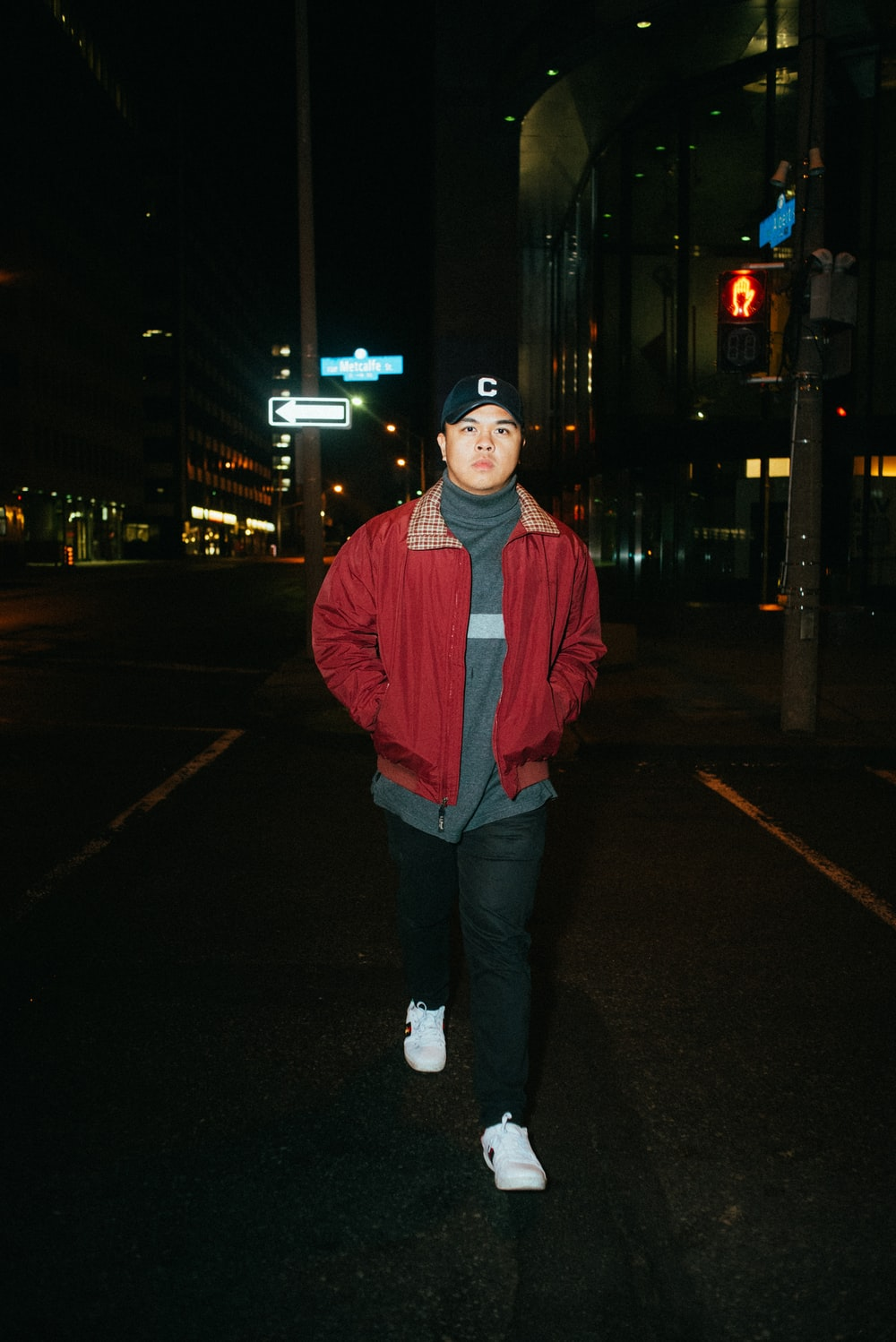 man in red jacket standing on sidewalk during night time
