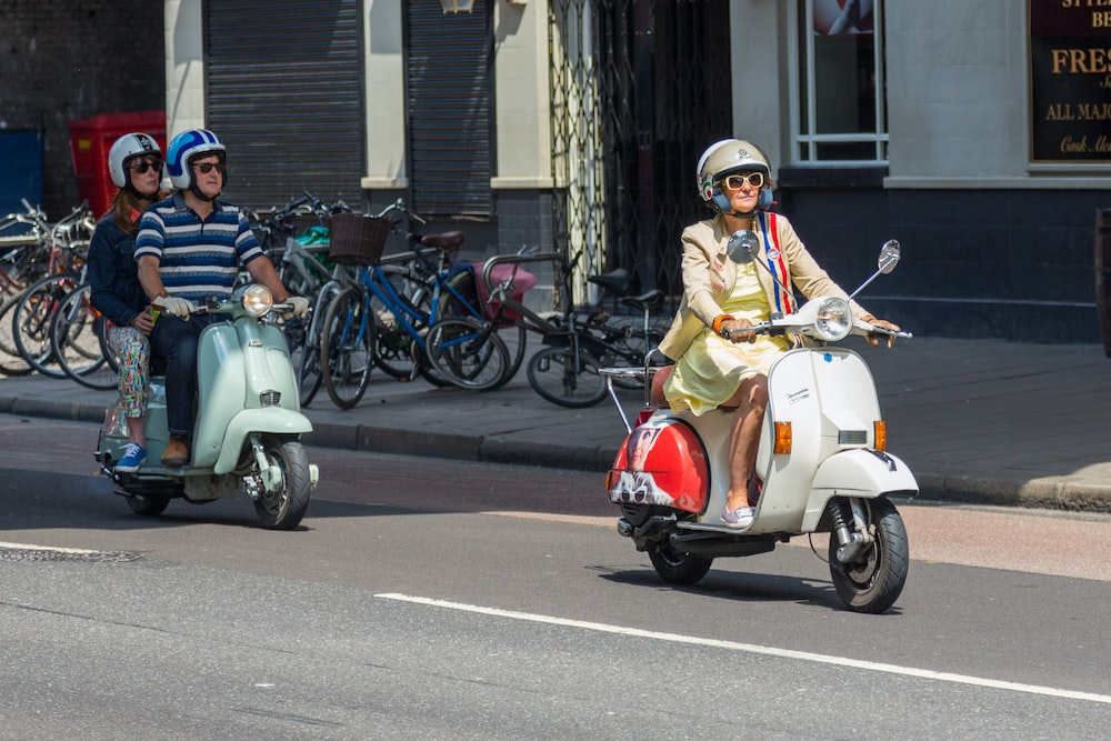 woman in yellow and white dress riding on white and red motor scooter during daytime