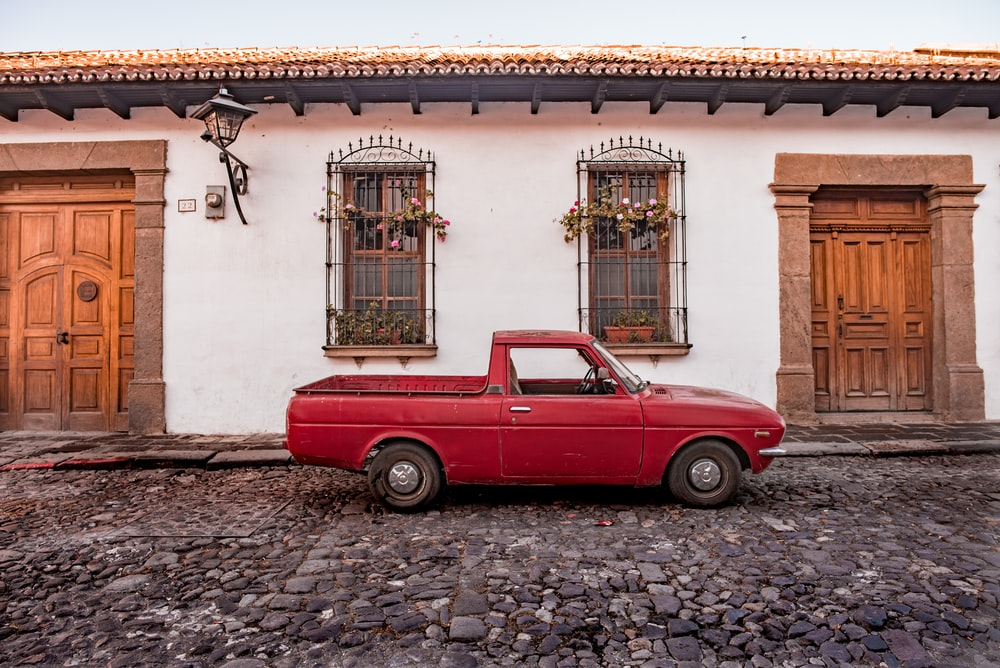 red vintage car parked beside white concrete building during daytime