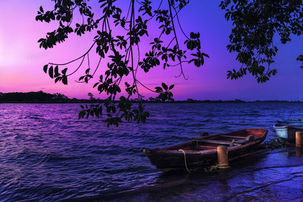 brown boat on body of water during sunset