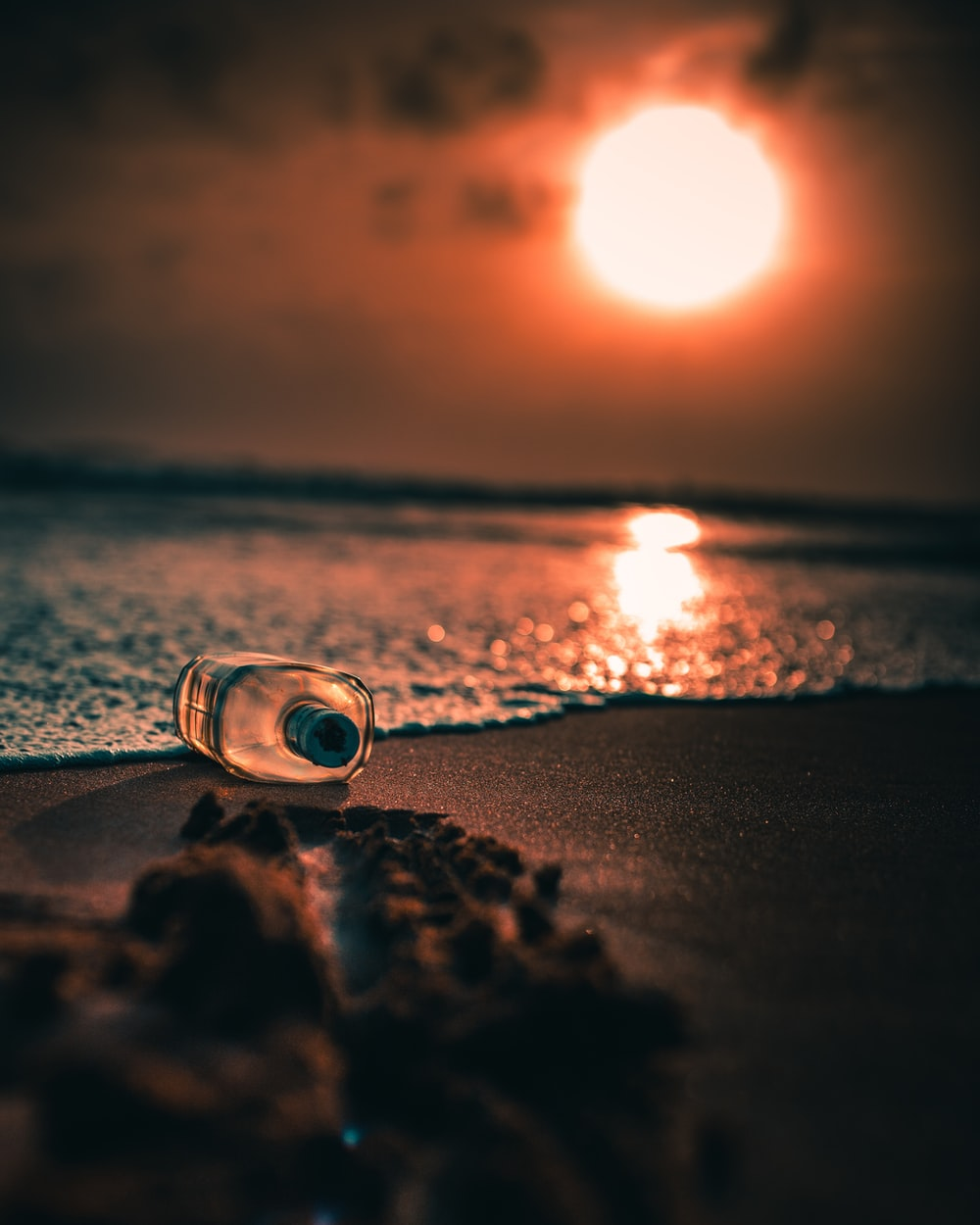 clear glass candle holder on beach shore during sunset