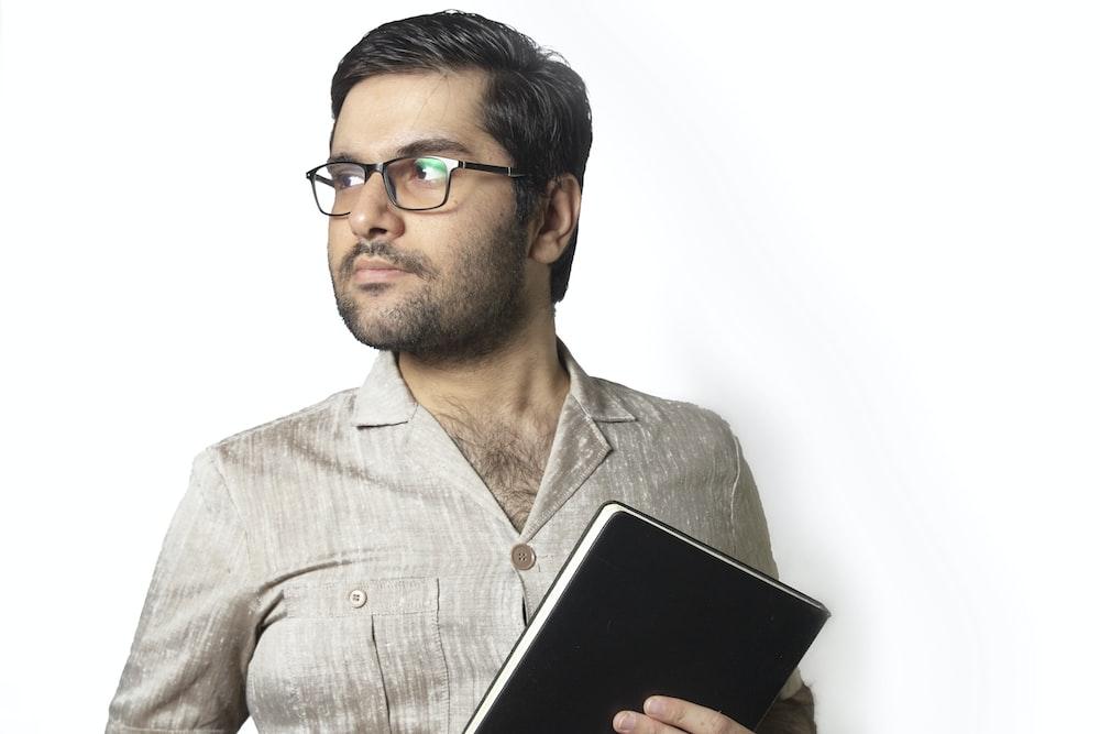 man in gray dress shirt holding black tablet computer