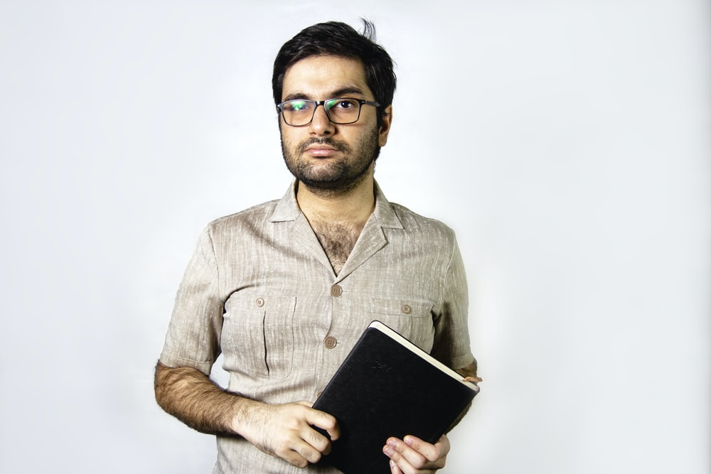 man in brown button up shirt holding black tablet computer