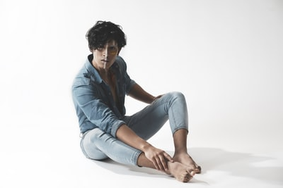 woman in blue denim jacket and blue denim jeans sitting on white floor conceptual art zoom background