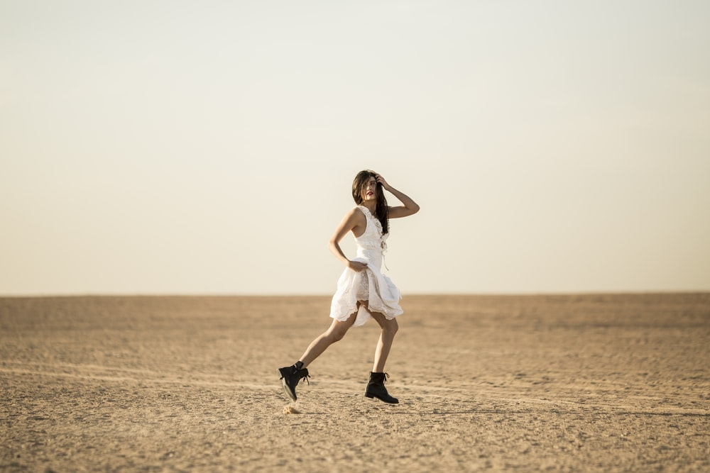 woman in white sleeveless dress standing on brown sand during daytime