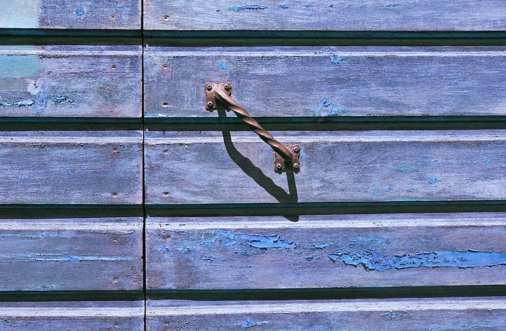 black metal hook on blue wooden wall