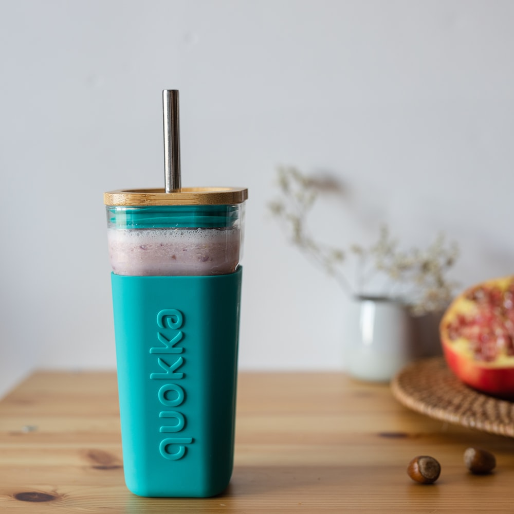 teal and white plastic cup on brown wooden table