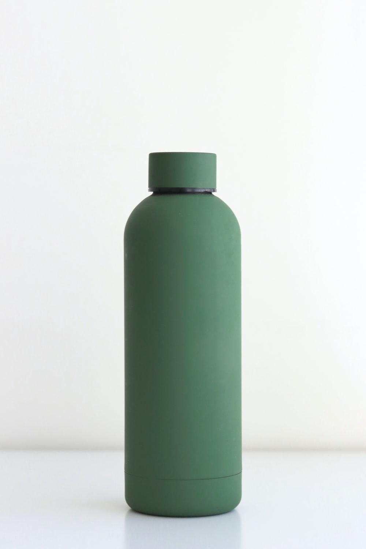 green bottle on white table