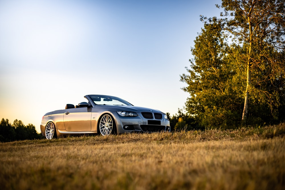 blue bmw m 3 coupe on brown grass field during daytime