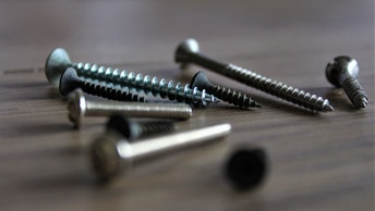 silver screw on brown wooden table