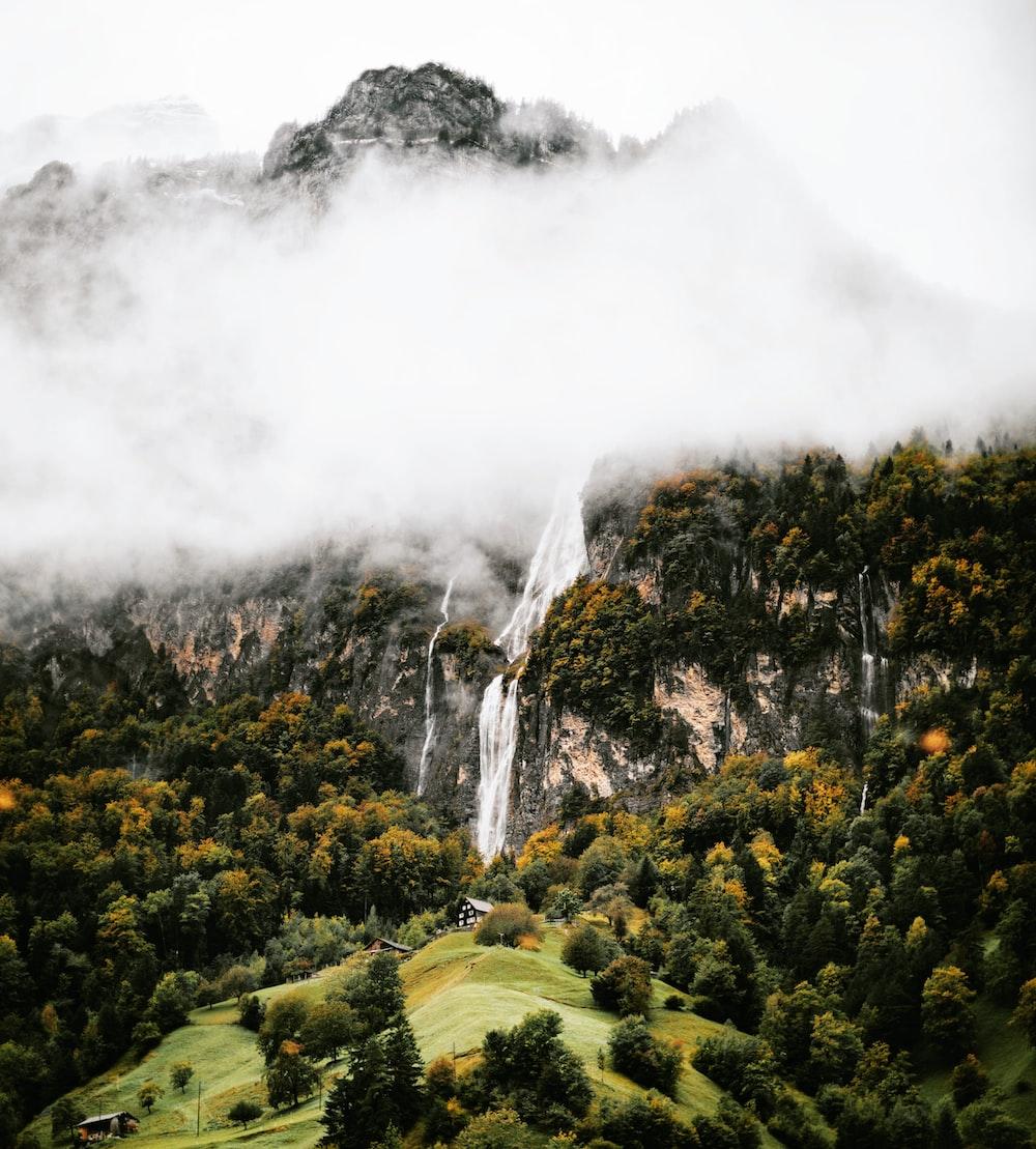 green grass field near waterfalls during daytime