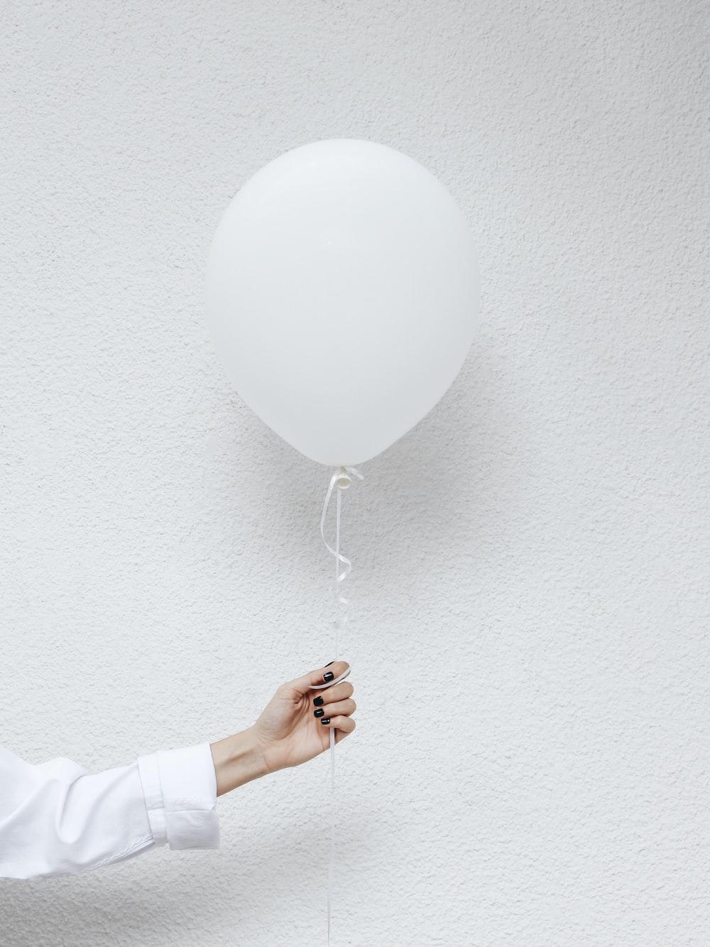 person holding white balloons near white wall