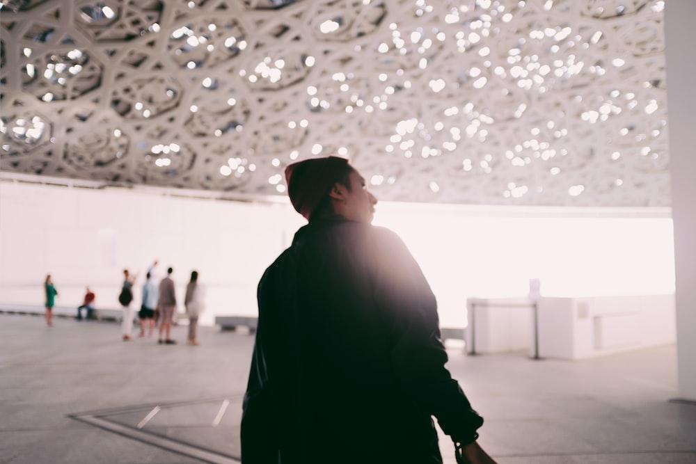 man in black jacket walking on gray concrete floor