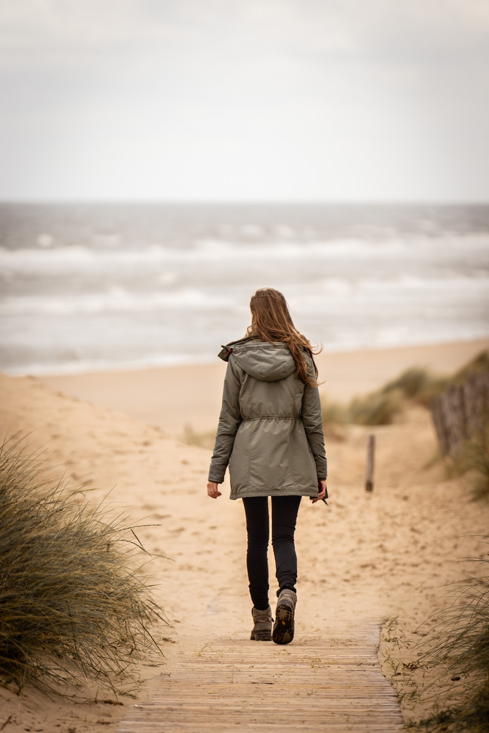 woman in brown coat standing on brown sand during daytime