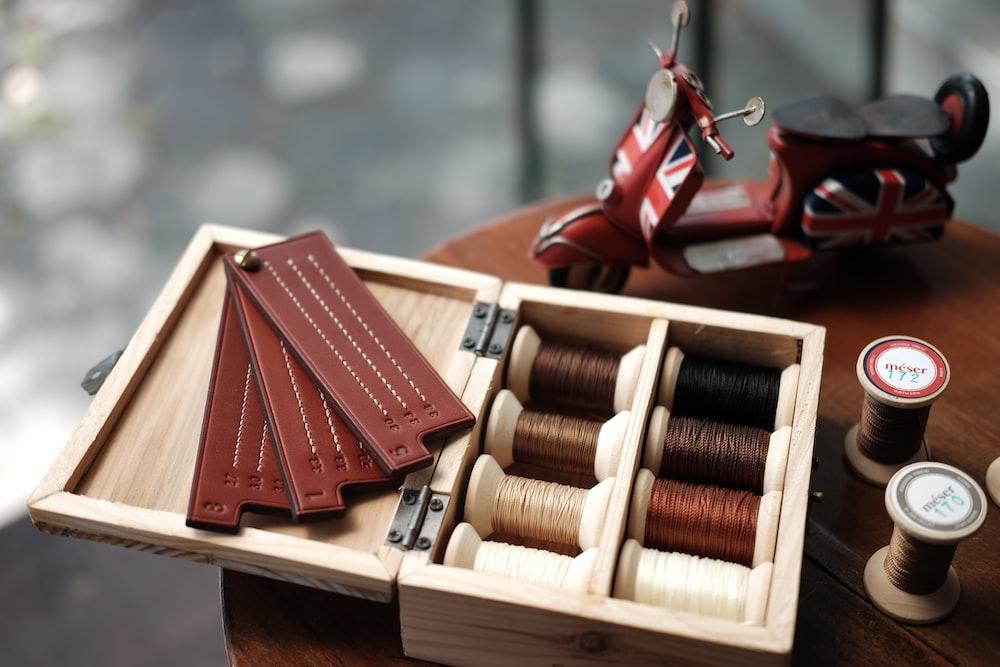 red hardbound books on brown wooden rack