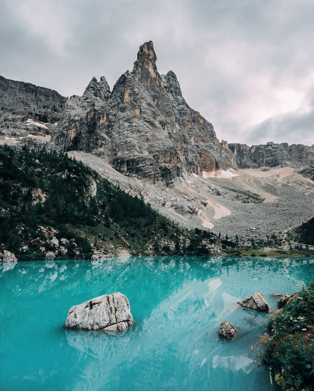 gray rocky mountain beside blue body of water during daytime