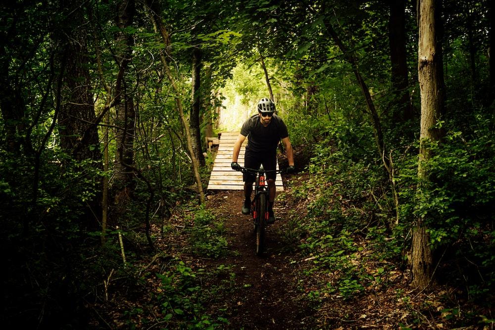 man in black jacket riding bicycle on brown wooden bridge