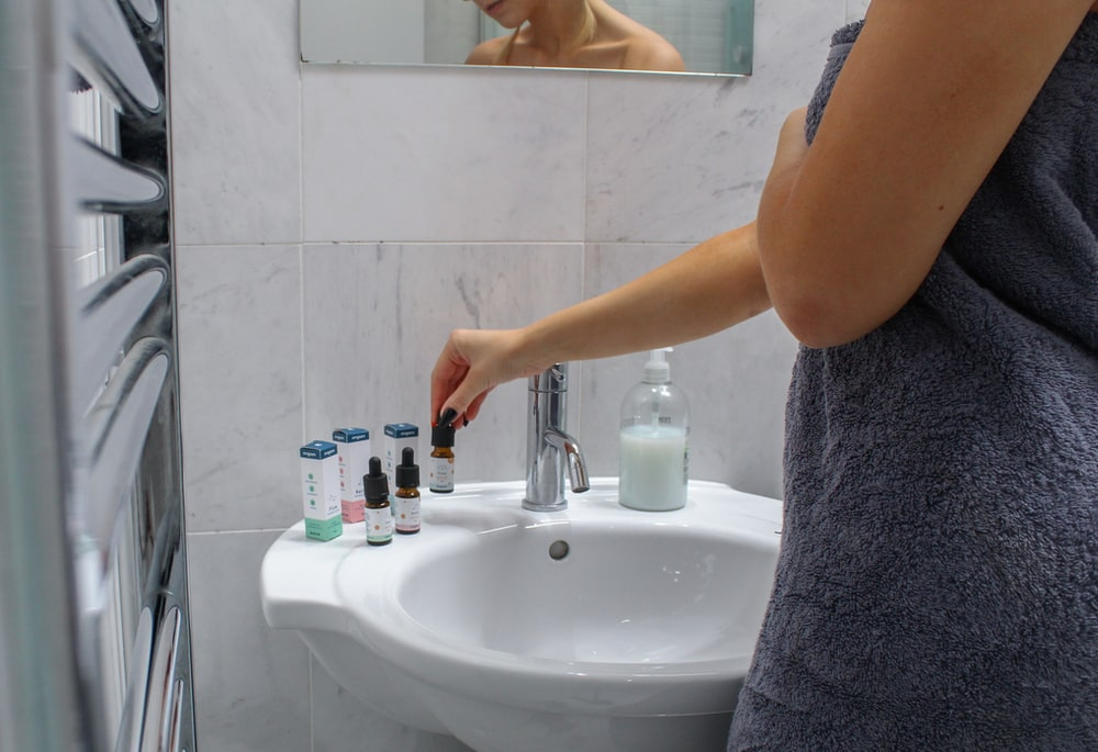 person holding white ceramic sink