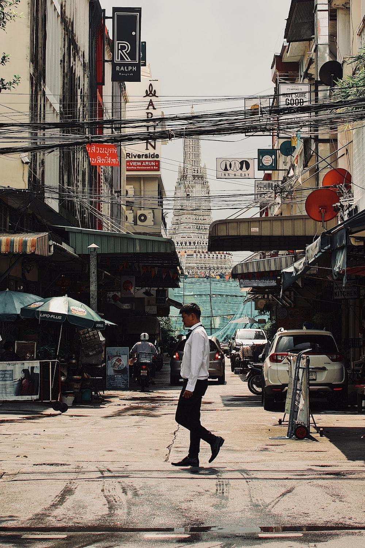 man in white dress shirt and black pants walking on sidewalk during daytime