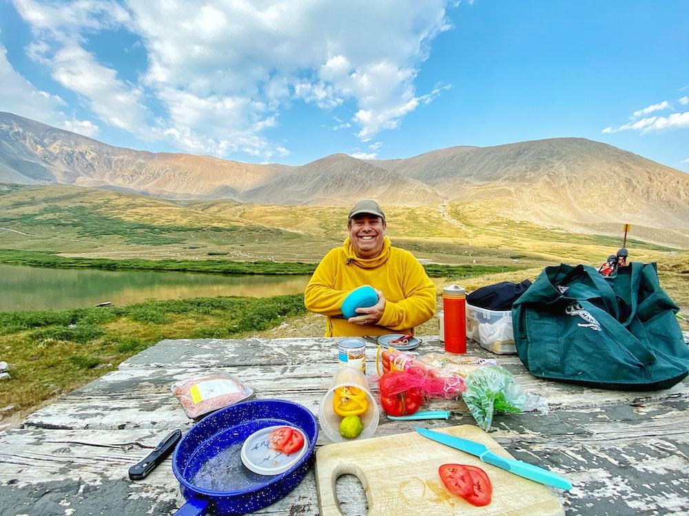 man in yellow crew neck t-shirt sitting on ground near mountain during daytime