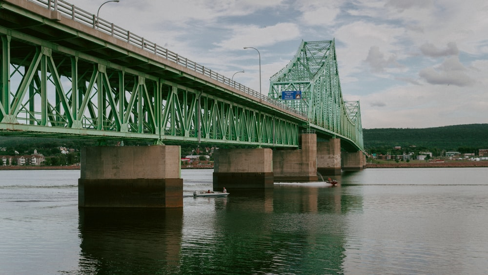 green bridge over river under cloudy sky during daytime
