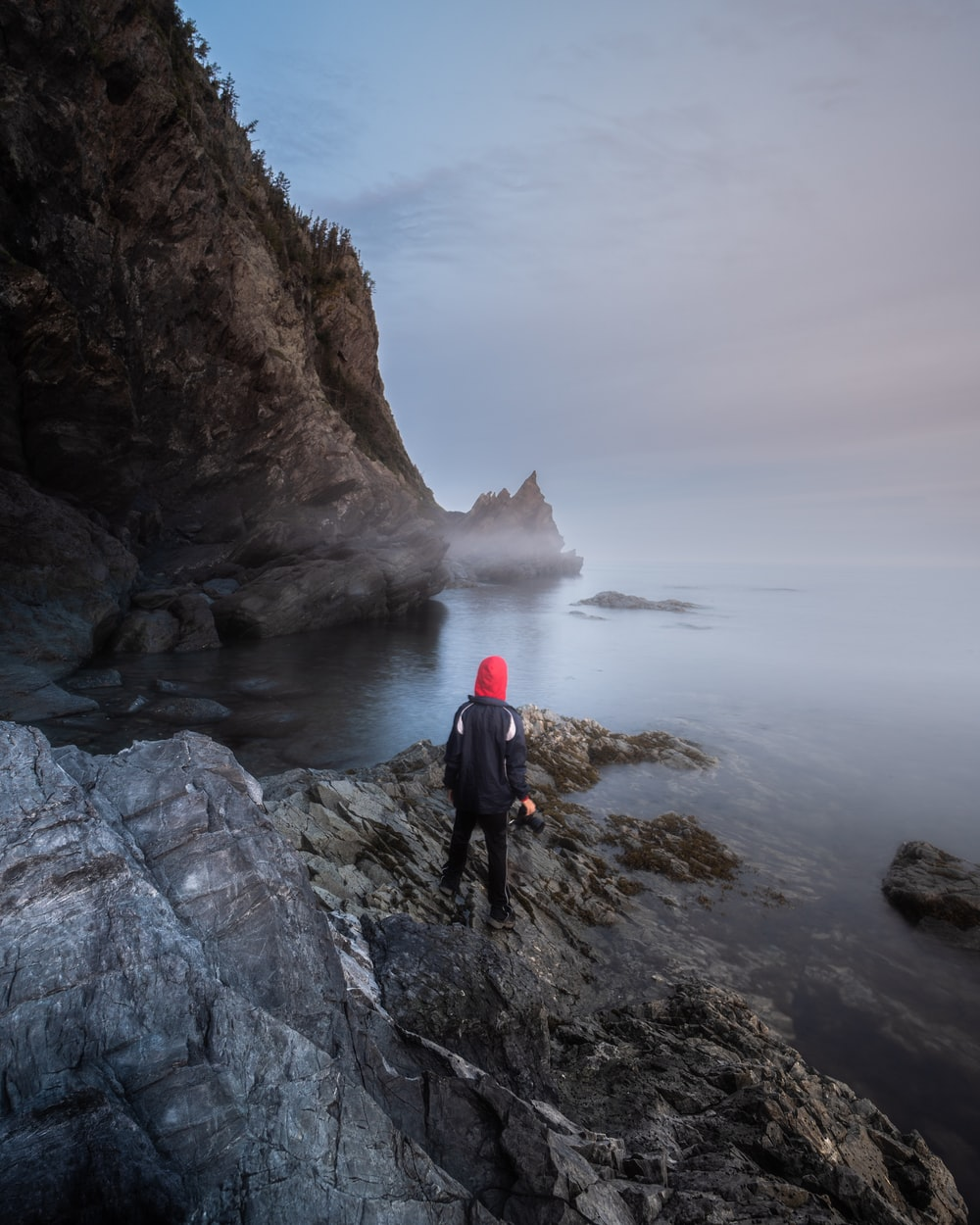 person in black jacket standing on rock formation near body of water during daytime