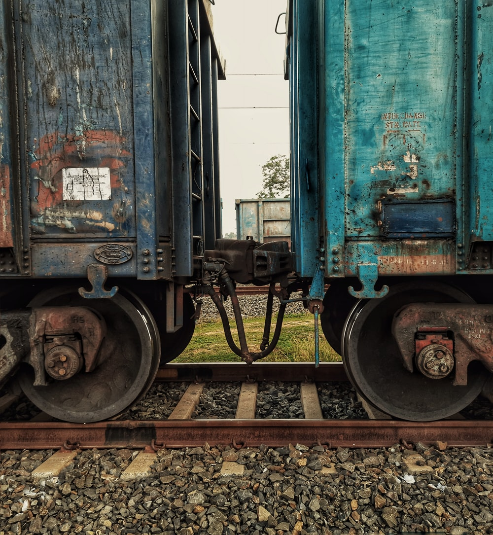 blue train on rail tracks during daytime