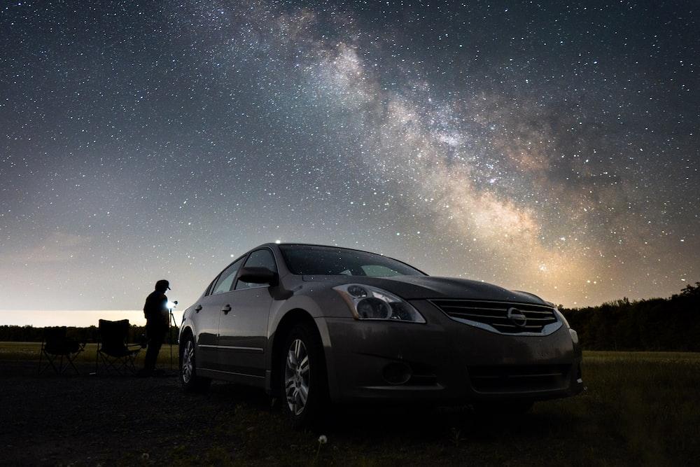 2 men standing beside black car under starry night