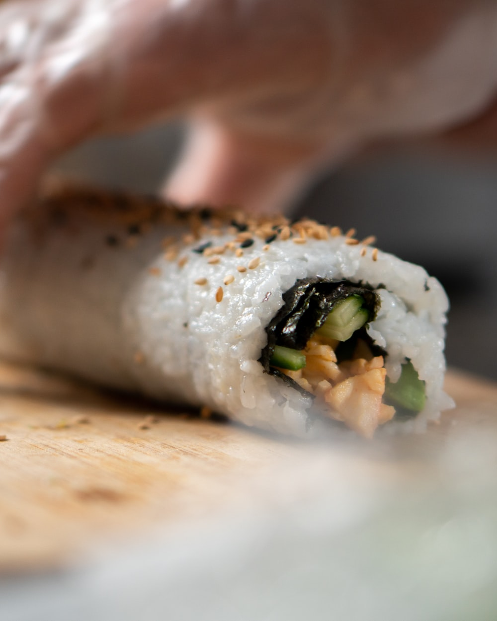 person holding sushi roll on brown wooden table
