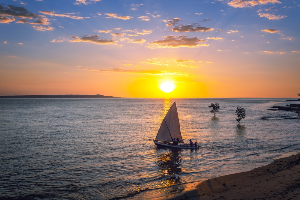 silhouette of people riding on sail boat on sea during sunset