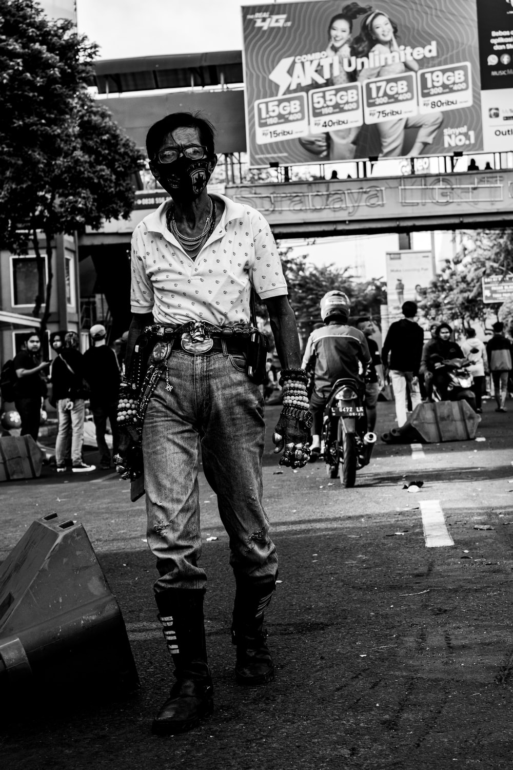 man in white t-shirt and blue denim jeans standing on street