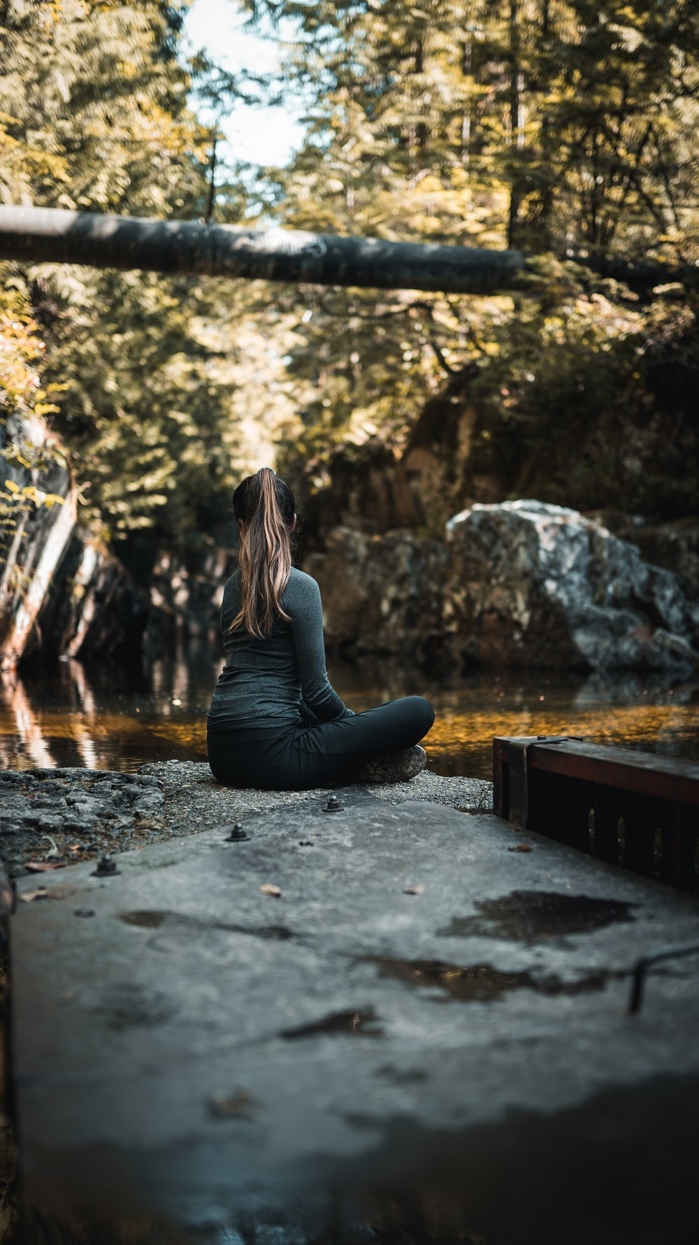 woman in gray long sleeve shirt and blue denim jeans sitting on brown wooden bench