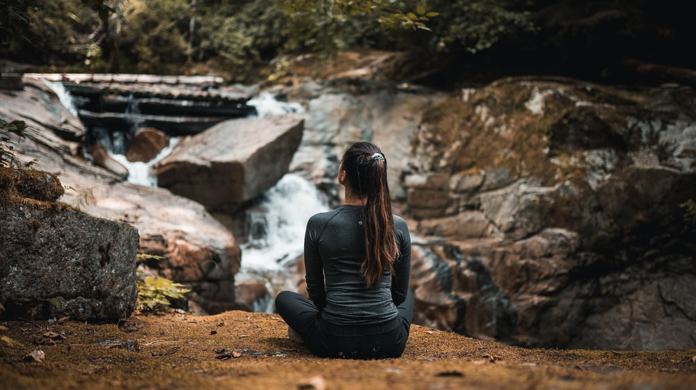 woman in black long sleeve shirt sitting on brown rock near river during daytime