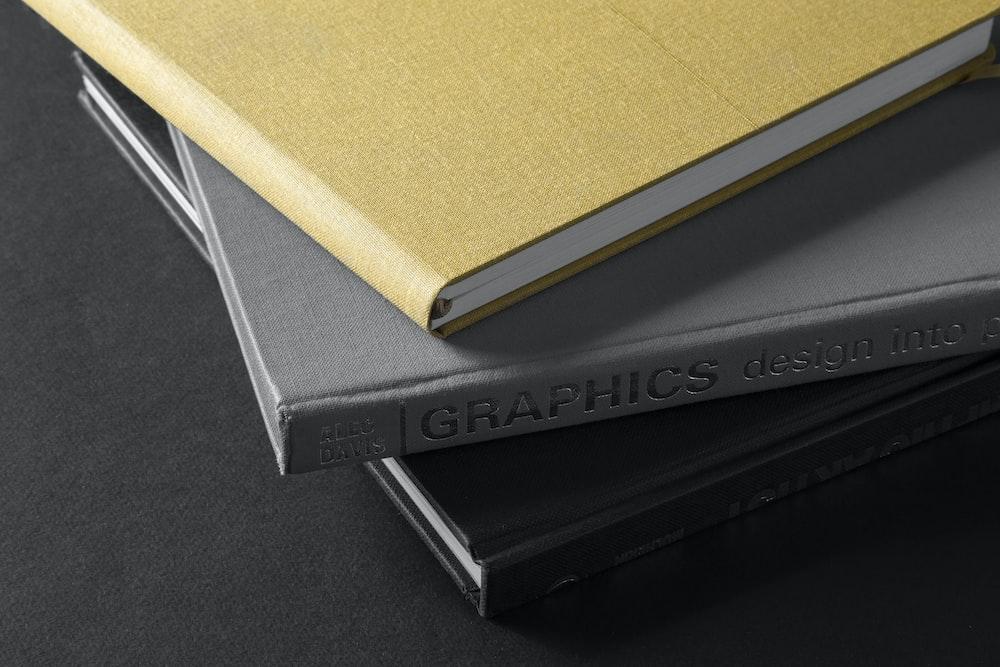 brown hardbound book on black book
