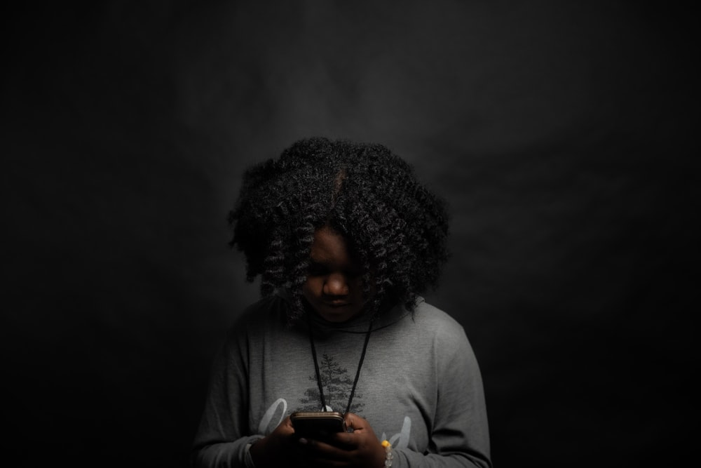 woman in gray long sleeve shirt holding black smartphone