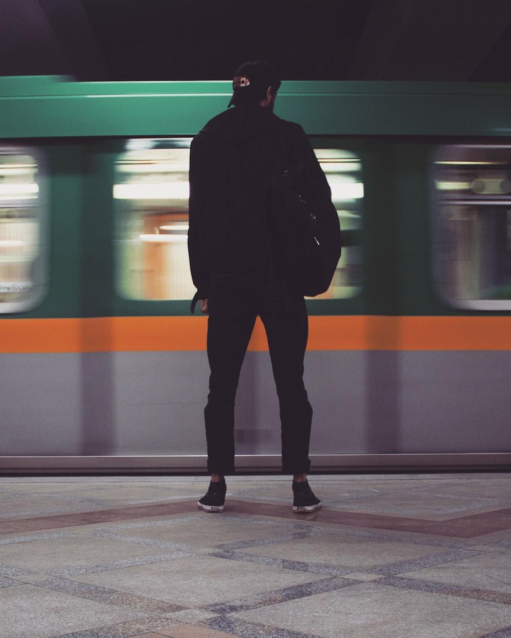 man in black jacket standing beside train