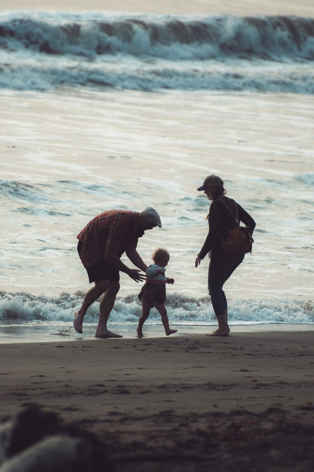 man in black jacket carrying child in red jacket on beach during daytime