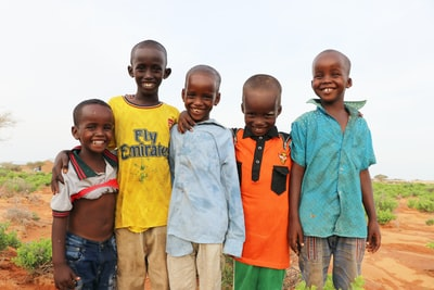 3 boys and 2 girls standing on green grass field during daytime somalia teams background